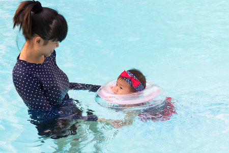 Asian young mother and cute eight month baby playing swimming pool, Active healthy first time playing swim in pool at home.