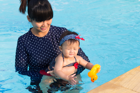 Asian young mother and cute eight month baby enjoy swimming pool, Active healthy first time playing swim in pool at home.