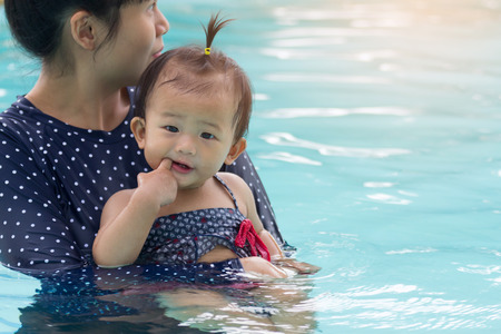 Asian young mother and cute one year baby playing swimming pool, Active healthy family playing swim in pool at home.