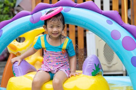 Photo pour Asian cute girl playing in inflatable baby pool. Kids swim and splash in colorful garden play center. Happy little girl playing with water toys on hot summer day. Family having fun outdoors in the backyard. Stay at home. - image libre de droit