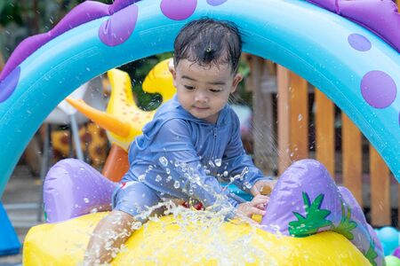 Photo pour Asian cute baby boy playing in inflatable baby pool. Kids swim and splash in colorful garden play center. Happy little girl playing with water toys on hot summer day. Family having fun outdoors in the backyard. Stay at home. - image libre de droit