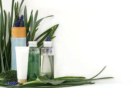 Foto de Reusable bottle with liquid. Skin care cosmetics on leaves flower and white background - Imagen libre de derechos