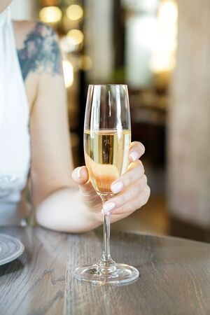 Photo pour Woman s hand with champagne glass and blur background of restaurant interior - image libre de droit