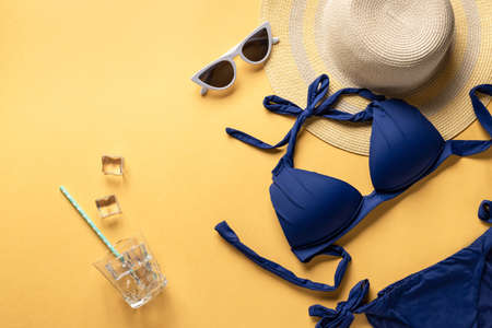 Photo pour Summer fun time and accessories on yellow background. blue swimsuit, straw hat and sunglasses. horizontal image, place for text - image libre de droit