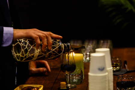 The bartender pours the liqueur into the glass and heats it in the candle.