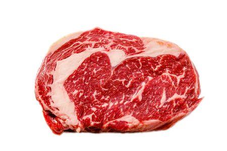 Foto de A rib eye steak of marbled grain-fed beef lies on a white background. Isolated. - Imagen libre de derechos