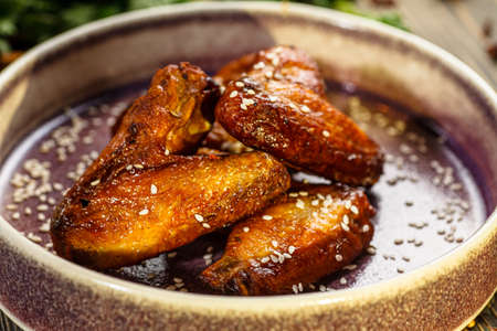 Photo pour Baked chicken wings in sauce and sprinkled with sesame seeds are on a plate - image libre de droit