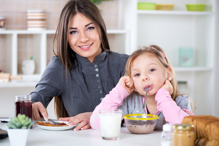 Mother and her daughter preparing breakfast  Mother smear jam on bread  Daughter fool around with cereal in milk  Looking at camera