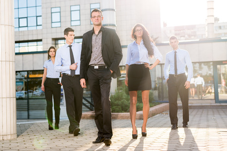 Young businessman, elegantly dressed with his hand in his pocket, standing proudly with his team of young businesswomen and businessmen in front of office building illuminated backlit sun.