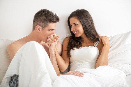 Young heterosexual couple in bed. Handsome guy holding his pretty girlfriend's hand and kissing her hand.