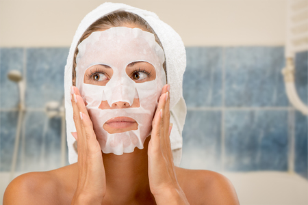 Beautiful young woman applying cosmetic facial mask in the bathroom.の写真素材