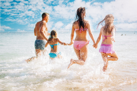 Foto de Happy family having fun on the beach. They with holding hands running and splashing in the sea. - Imagen libre de derechos