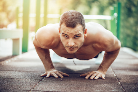 Young sportsman doing push-up exercise in the park. Looking at camera. Selective focus.