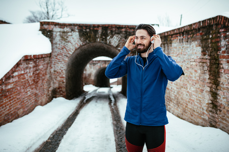 A male runner wearing headphones and preparing to running in the public place during the winter training outside in. Copy space.