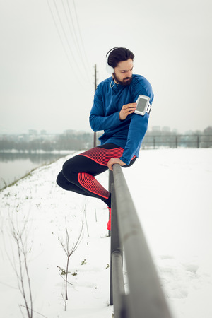 A male runner with headphones on his ears taking a break and checking his mobil phone in the public place during the winter training outside in. Copy space.
