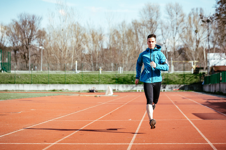 Athletic fit young sport man in full body length on tartan track on the stadium.