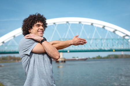 Sport guy stretching before exercises near the river. Copy space.