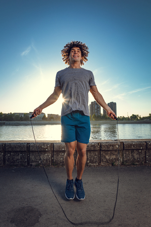 Young handsome sport guy skipping rope near the river against blue sky with sunrise light.