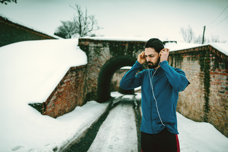A male runner with headphones on his ears prepare to run in the public place during the winter training outside in. Copy space.