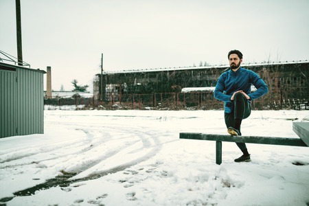Active young  man stretching and doing exercises in the public place during the winter training outside in while it snowing. Copy space.