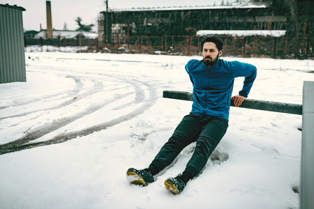 Active young  man stretching and doing exercises in the public place among old railroad during the winter training outside in. Copy space.