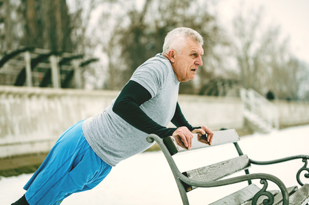 Active senior man athlete doing push ups on the bench and doing exercises by the river during the winter training outside in. Copy space.