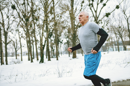 Active senior man running and doing exercises in public park during the winter training outside in. Copy space.