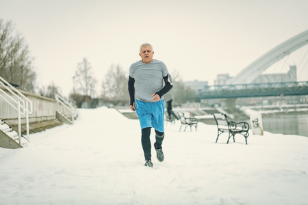 Active senior man running and doing exercises by the river during the winter training outside in. Copy space.