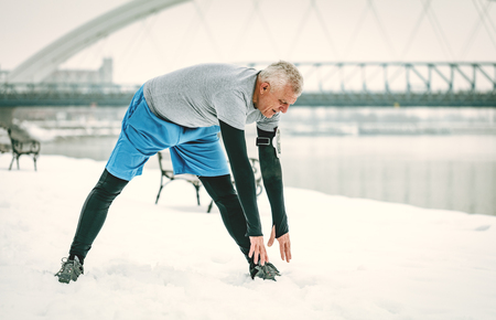 Active senior man stretching and doing exercises by the river during the winter training outside in.