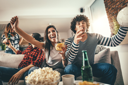 Foto de Friends are fans of sports games as football love spending their free time at home together. They are screaming and gesturing for a victory. - Imagen libre de derechos