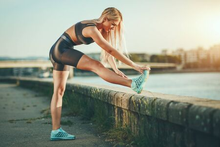Young fitness woman doing stretching exercise by the river wall, preparing for morning workout.