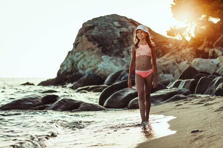 Photo pour Cute teenager girl is walking along the sea shore in the end of the day. - image libre de droit