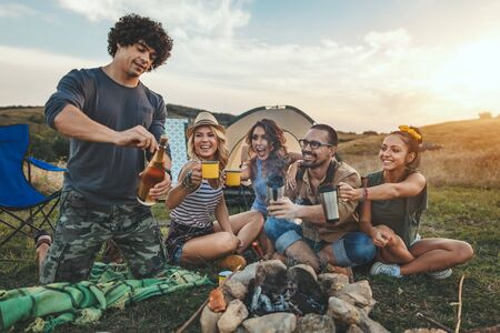 Photo for Happy young friends enjoy a nice day in nature. They're grilling sausages, eating, drinking  champagne, laughing and talking happy to be together. - Royalty Free Image