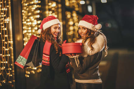 Photo for Two female friends enjoy the winter night and laughing with shopping bags and red box in their hands. - Royalty Free Image