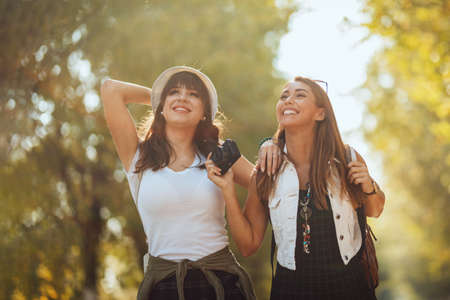 Photo pour Two beautiful young smiling women with backpacks on their back are walking along the autumn sunny avenue and looking away. - image libre de droit