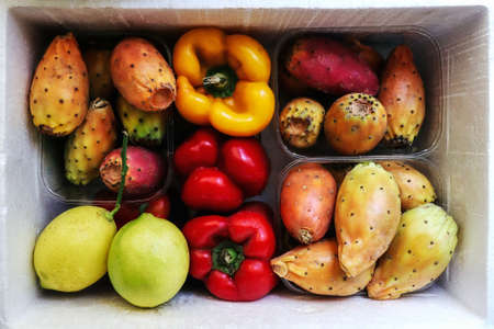 Foto per Colorful fresh and raw fruits and vegetables: prickly pears, opuntia cactus figs, raw yellow and red pepper bells and lemons in white box at street market top view photo. Frutta e verdura Italiana. - Immagine Royalty Free