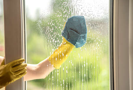 Photo for A female hand in a yellow glove washes a dirty window in the summer. Rag in hand. Cleaning of the apartment. - Royalty Free Image