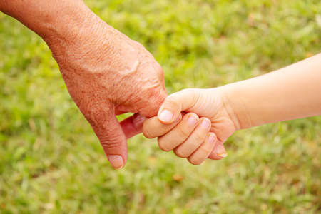 Photo for old man holding child's hands. selective focus.people - Royalty Free Image