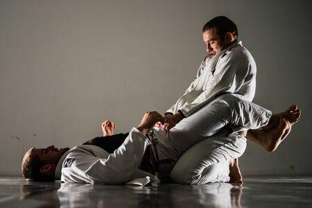 Foto de Brazilian jiu-jitsu BJJ training sparing on the tatami two fighters in guard position in training - Imagen libre de derechos