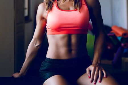 Photo for Midsection of young muscular fit fitness woman sporty sportswoman sitting on the bench at the gym posing her muscles - Royalty Free Image