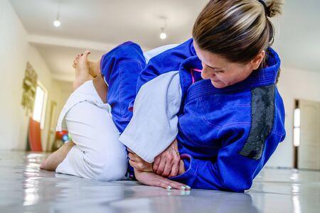 Foto de Woman in brazilian jiu jitsu bjj training judo kimura attack arm lock from the guard position submission attemp - Imagen libre de derechos