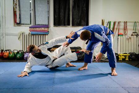 Foto de Brazilian Jiu Jitsu BJJ martial arts training sparring at the academy two fighters in technical stand up guard position drilling techniques practicing in a gi kimono self defense - Imagen libre de derechos