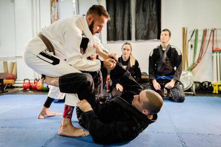 Foto de Brazilian Jiu JItsu BJJ professor teaching technique from the guard position to his students in training class at the martial arts academy - Imagen libre de derechos