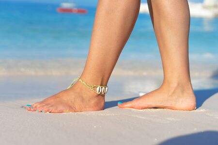 Photo pour Girl standing barefoot on the sand beach female feel walking in summer vacation sunny day by the sea or ocean - image libre de droit