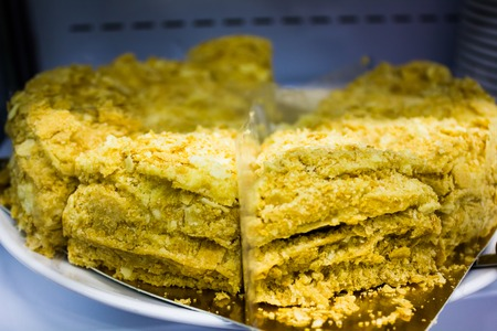 Large honey cake with gold powder on the counter