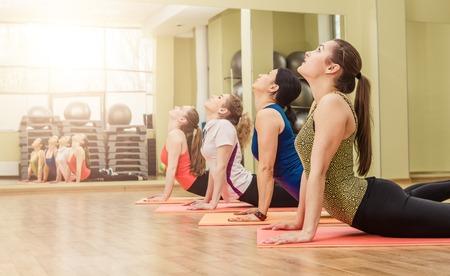Foto de Group of women making step aerobics in the fitness class - Imagen libre de derechos