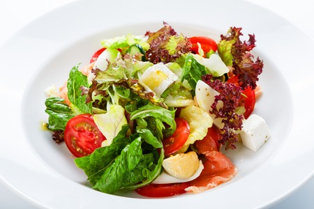 Restaurant healthy food, diet nutrition - fresh salad with salmon, quail eggs, cherry tomatoes and lettuce, closeup