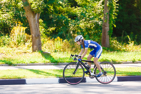 Photo pour Female sportsman cyclist riding racing bicycle. Woman cycling on countryside summer sunny road or highway. Training for triathlon or cycling competition. - image libre de droit