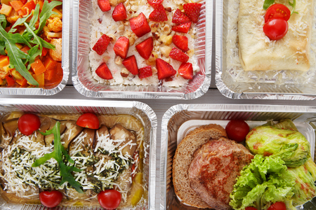 Healthy food background. Take away of natural organic food in foil boxes. Fitness nutrition, meat, vegetable and berry cereal. Top view, flat lay.の写真素材