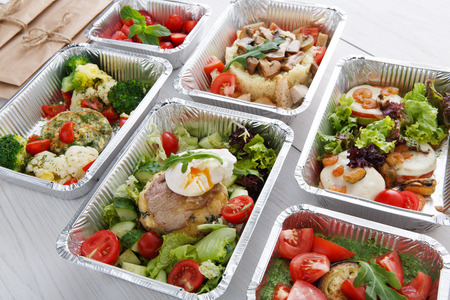Foto de Healthy food restaurant delivery and diet concept. Take away of fitness meal. Weight loss lunch in foil boxes. Poached egg with steak and other dishes at white wood - Imagen libre de derechos